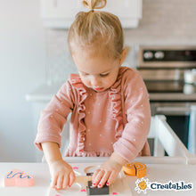Load image into Gallery viewer, young girl in all white little sidekicks smiles as she cuts a wooden brownie in half with a wooden knife