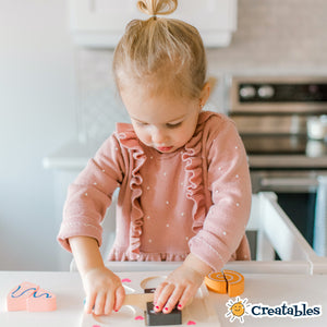 young girl in all white little sidekicks smiles as she cuts a wooden brownie in half with a wooden knife