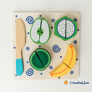wooden cutting toy with 4 fruit pieces and a wooden knife on a square tray decorated with blue swirls