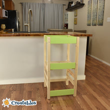 Load image into Gallery viewer, little sidekick learning tower in unpainted frame with green panels against a kitchen counter