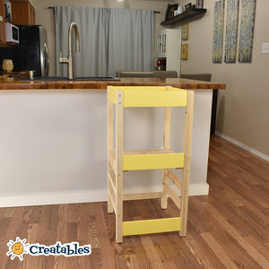 little sidekick learning tower in unpainted frame with yellow panels against a kitchen counter