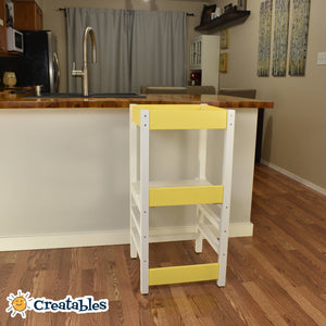 little sidekick learning tower in white frame with yellow panels against a kitchen counter