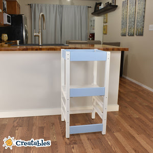little sidekick learning tower in white frame with blue panels against a kitchen counter