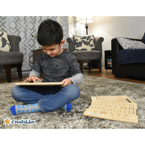 young boy sits in livingroom crossed legged smiling and tracing a wooden shape board