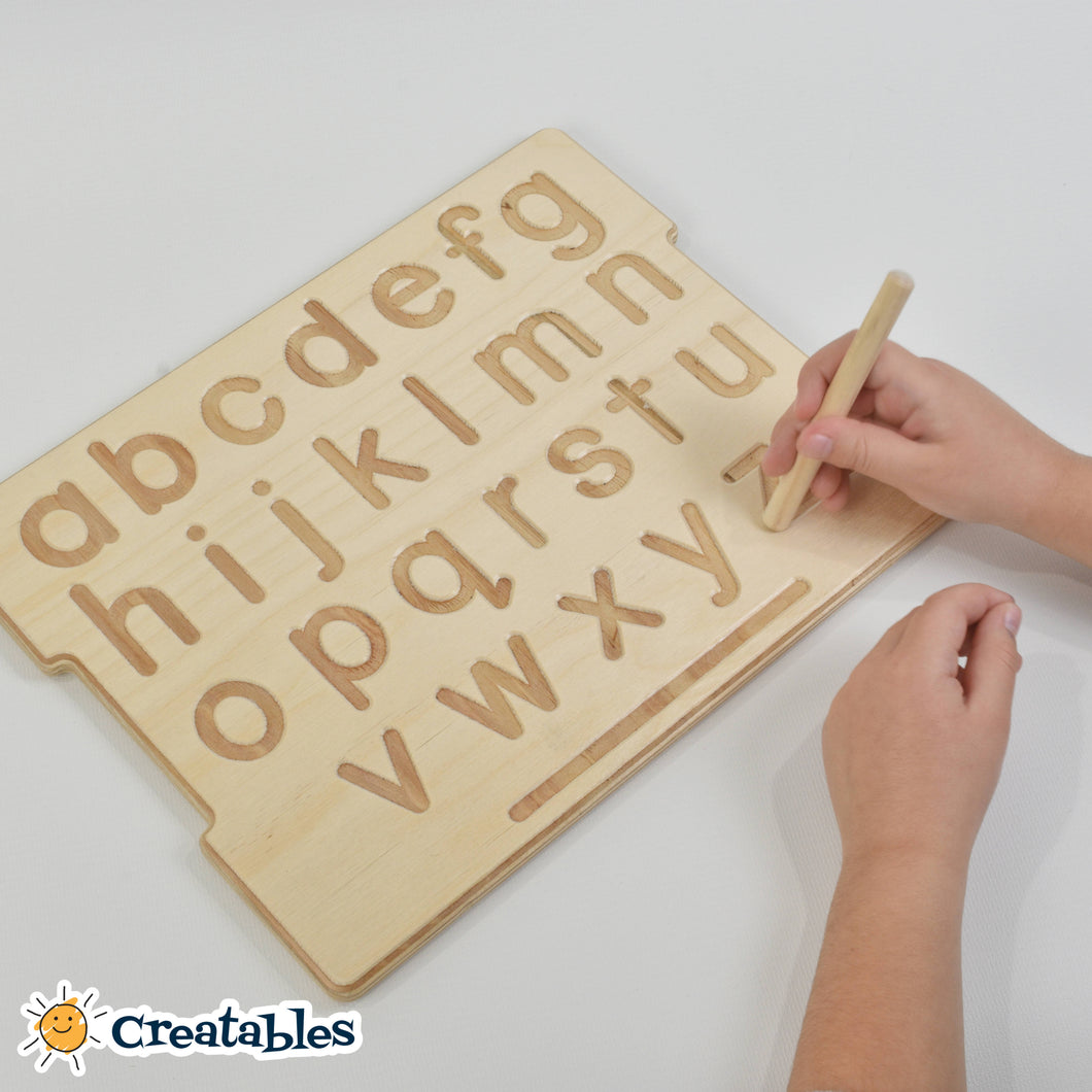 child hands hold a wooden pencil to trace a montessori alphabet wooden board