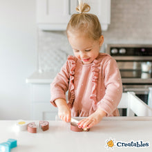 Load image into Gallery viewer, young girl is standing in little sidekick and smiling as she cuts a piece of wooden food in half with a wooden knife.