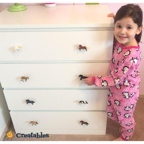 white dresser with pony drawer knobs Girl in pink pajamas is next to it smiling