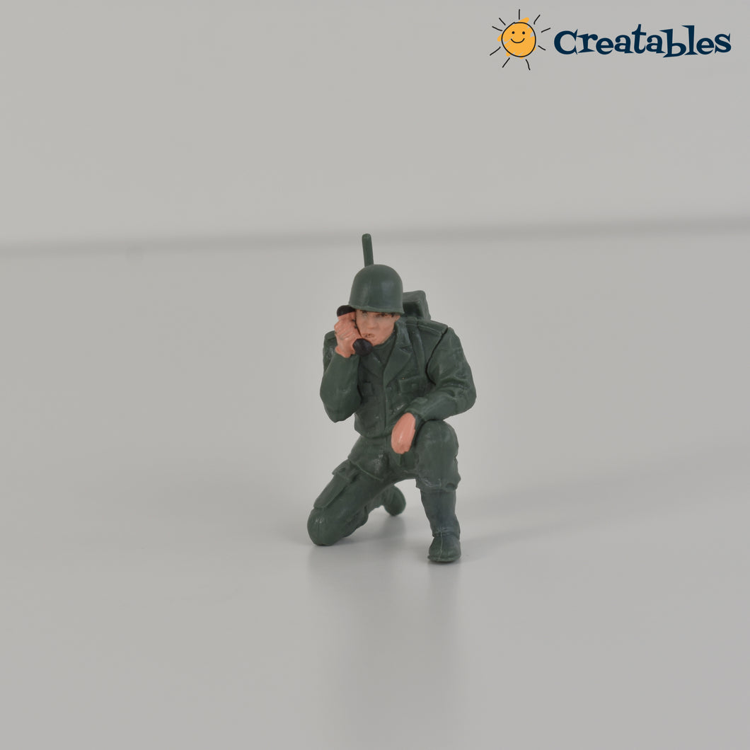 army man kneeling and talking on the radio front view