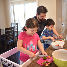 Load image into Gallery viewer, young girl in pink and white learning tower and young boy in white and blue learning tower cut strawberries with dad watching and are happy