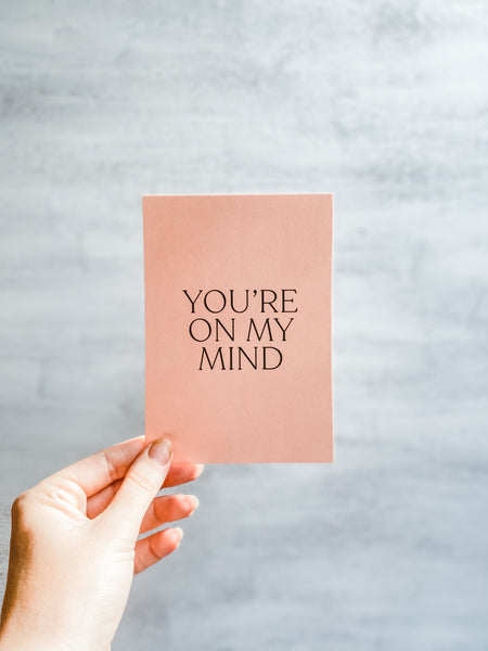 "This is an image of our 'You're on my Mind"" Mini Postcard. It's an A6 postcard that can be added to your flower delivery, and features forest green text in all caps on a ballet pink background."