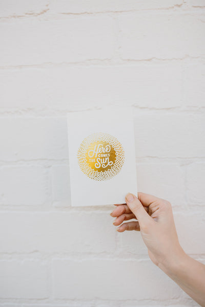 This is an image of our 'Here Comes The Sun' Greeting Card. It's an A6 card that can be added to your flower delivery, and features gold foiled and letterpressed text in an illustration of a chrysanthemum, on a thick white stock.