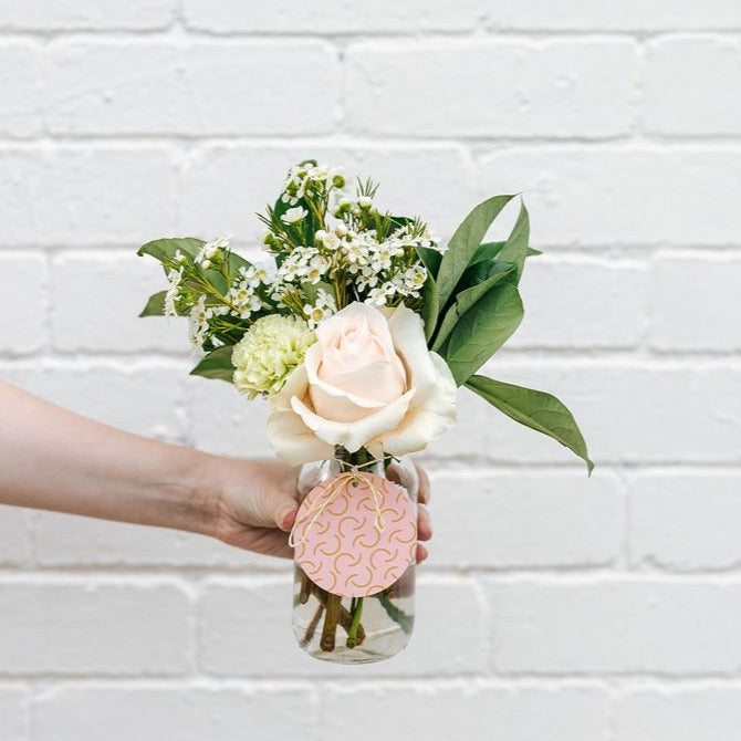 A little jar of love held against a white brick wall  featuring a cream rose,  green carnation, white wax flower and viburnum, with a pink and yellow patterned tag appropriate for sympathy.