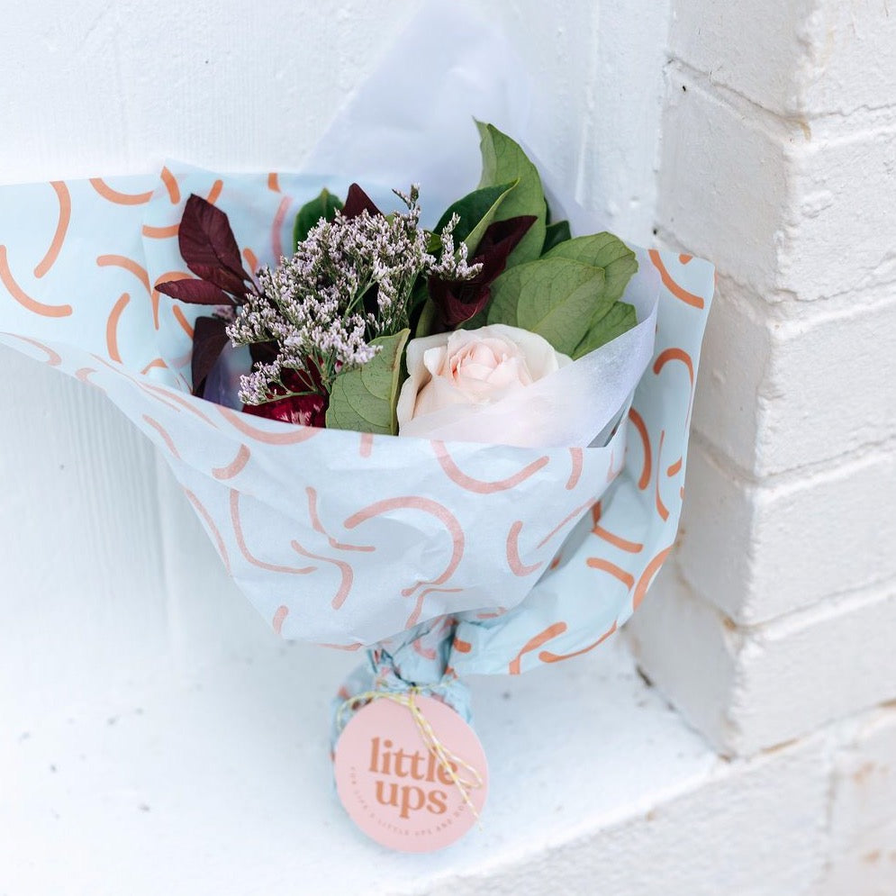 A little bunch of happiness featuring one cream rose, burgundy carnation, purple misty and viburnum foliage with a Little Ups swing tag and our custom patterned tissue against a white brick wall.