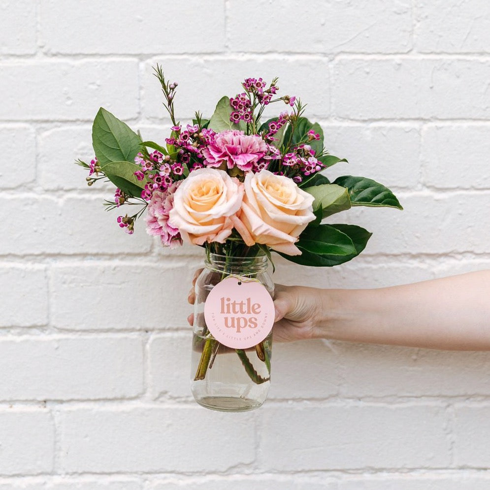 A double jar of happiness featuring two peach roses, pink carnations, pink wax flower and viburnum foliage with a Little Ups swing tag against a white brick wall.