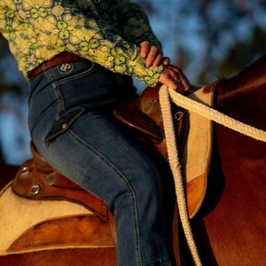 Woman wearing jeans in saddle
