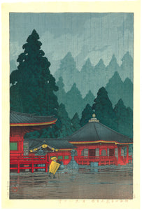 Hasui: A priest walks in the rain in front of Futatsu Hall, Nikkô. From a limited edition, published by Sakai and Kawaguchi.