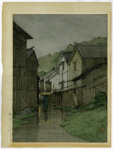 Hasui: Watercolor of an umbrella-carrying pedestrian entering a quiet village in the rain at dusk. There is no known print that corresponds to this image.