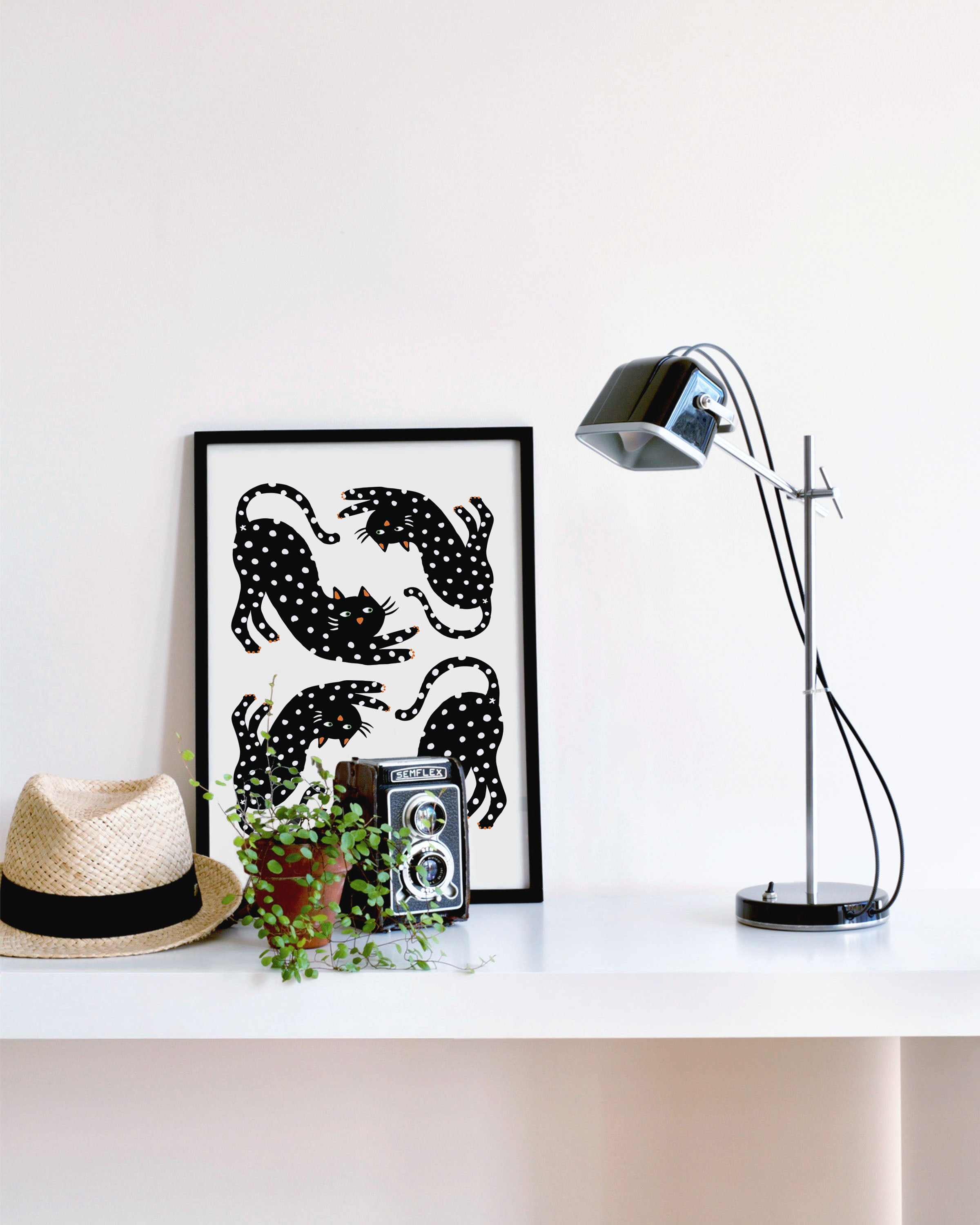 Playful Black Cat Art Print in a black frame surrounded by a plant, hat and desk lamp