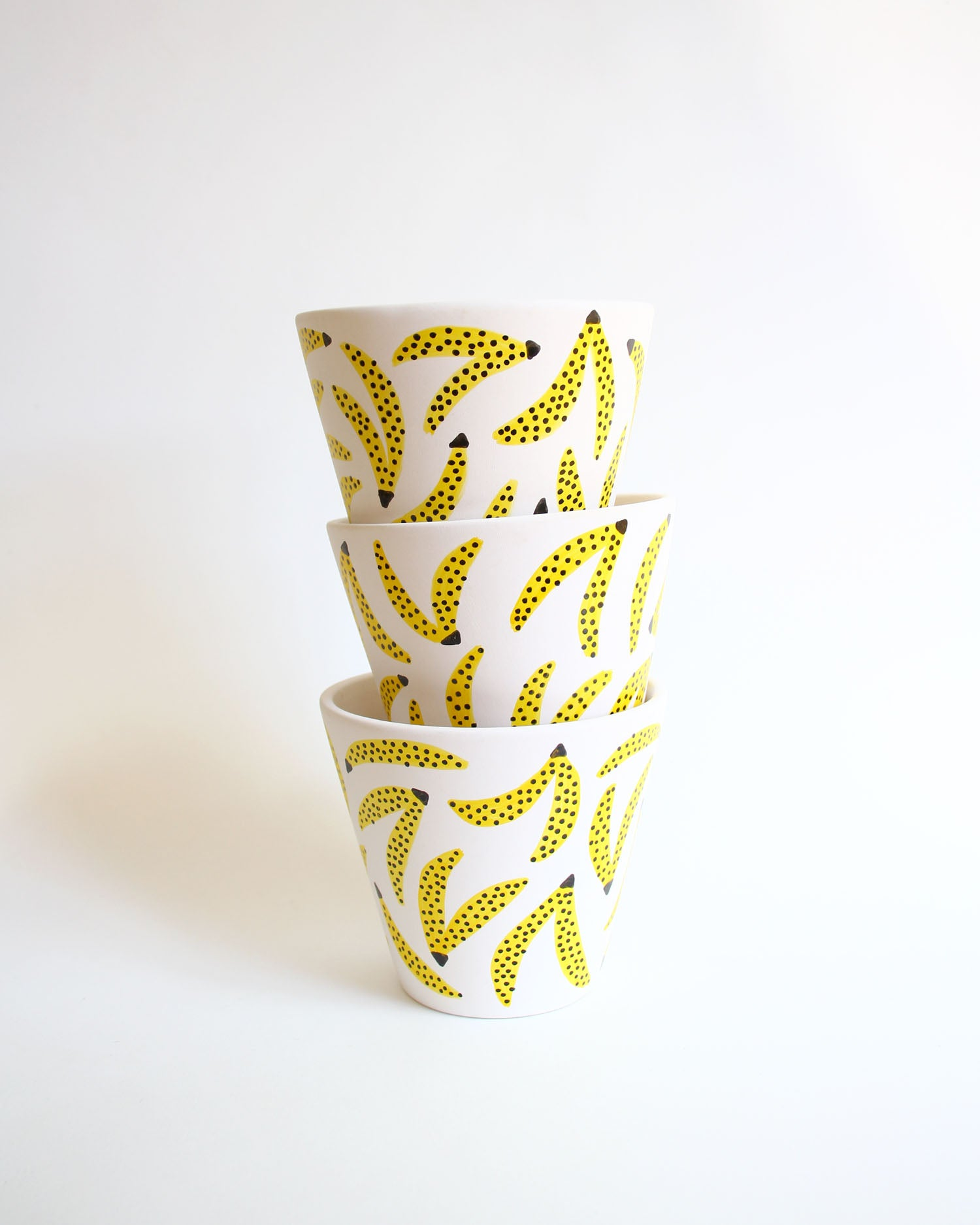 A stack of 3 banana pattern planter pots