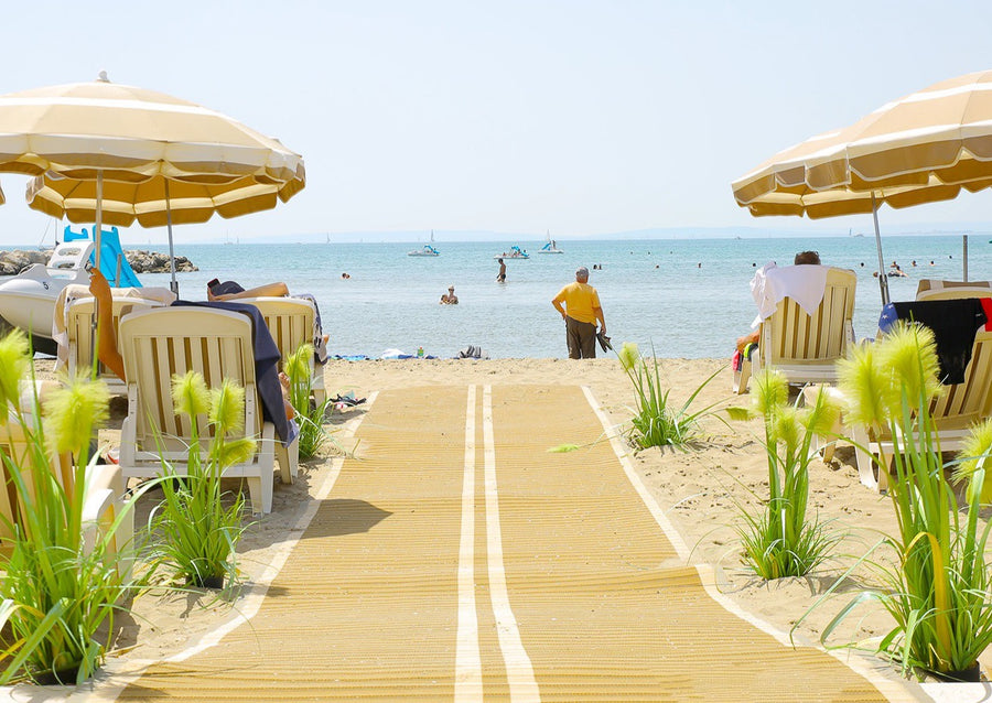 Photograph of Mobi- Path / Roadway running along sand down towards the sea and a beach with beach umbrellas and chairs either side of the path. There are green and yellow plants either side of the path and people and boats in the sea.