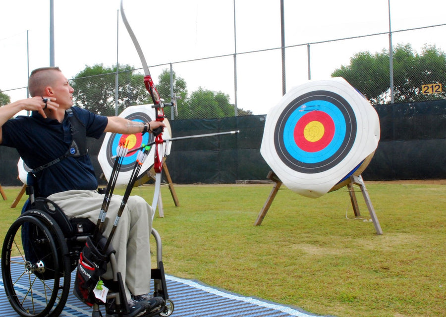 Photograph of a disabled archer on a blue Mobi- Path / Roadway that has been rolled out on grass, shooting an arrow at a bright target