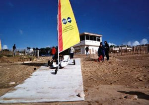 A Mobi-Boat Ramp has been rolled out on a sandy and slightly rocky surface from a sailing clubhouse presumably down to water. A sailing boat with a bright yellow and red sail on a trailer in being wheeled along the ramp while a couple people watch. There is a bright blue sky in the background.