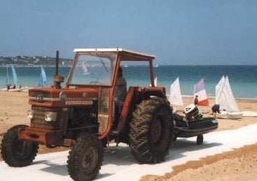 A Mobi-Boat Ramp has been rolled out on sand on a beach. An old red tractor has pulled a dingy out of the water and is pulling it along the boat ramp