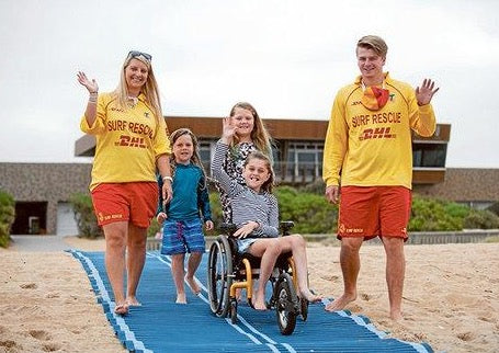 Mob-Path being used on the beach by a child in a three wheeled wheelchair with two surf lifesavers and two other children