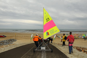 Sailing boat with bright yellow and pink sail being rolled on wheels along a Mobi-Boat Ramp mat that has been rolled out on sand on a long beach