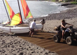 A brown Mobi-Boat Ramp has been rolled out on sand on a sandy and rocky beach. A catamaran is attached to a quad bike by a rope and is being pulled up the ramp. Two additional people are assisting to guide the direction of the catamaran.