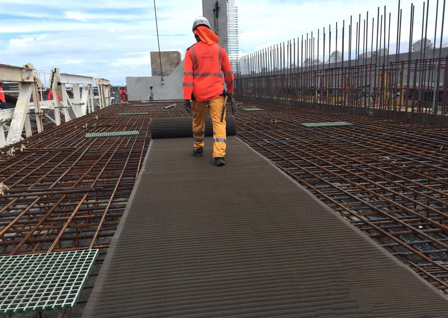 Photograph of a workman rolling out a Mobi- Path / Roadway along reinforced iron mesh at a construction site. Walking away from photographer.