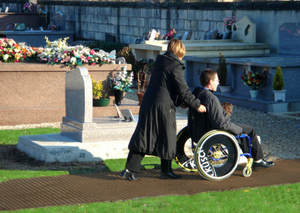 A disabled person in a wheelchair with a  dog on his lap is being pushed a long a brown Mobi- Path / Roadway that has been rolled out on grass in a cemetery