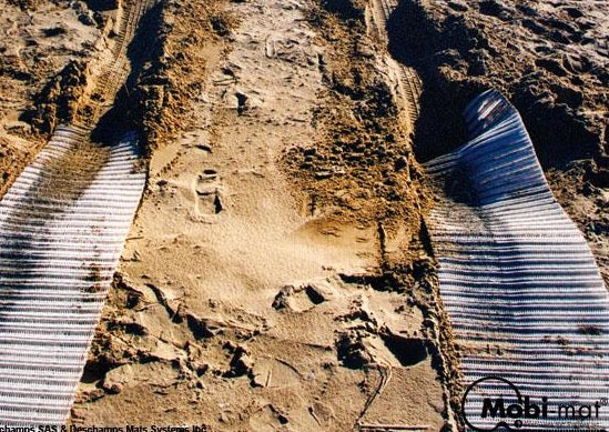 Photo of two white Mobi-Tracks rolled out on sand.