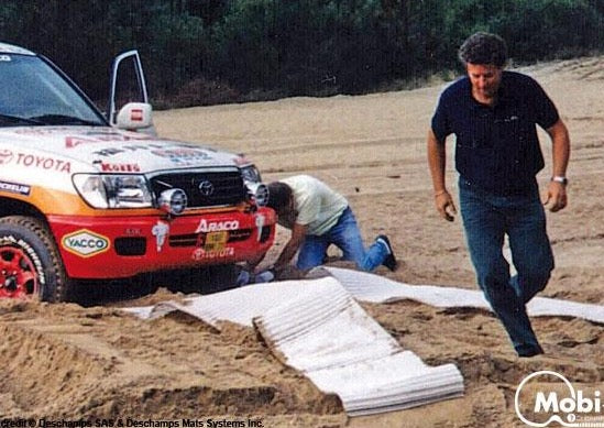 Photo of a bogged 4WD on rugged sandy ground with two men setting up white Mobi-Tracks under the cars wheels.