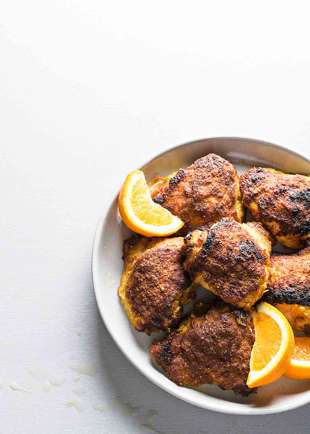 These orange ginger chicken thighs are an easy meal made by marinating chicken in a mixture of ginger, oranges, and soy sauce, then roasting to crispy-skinned perfection.