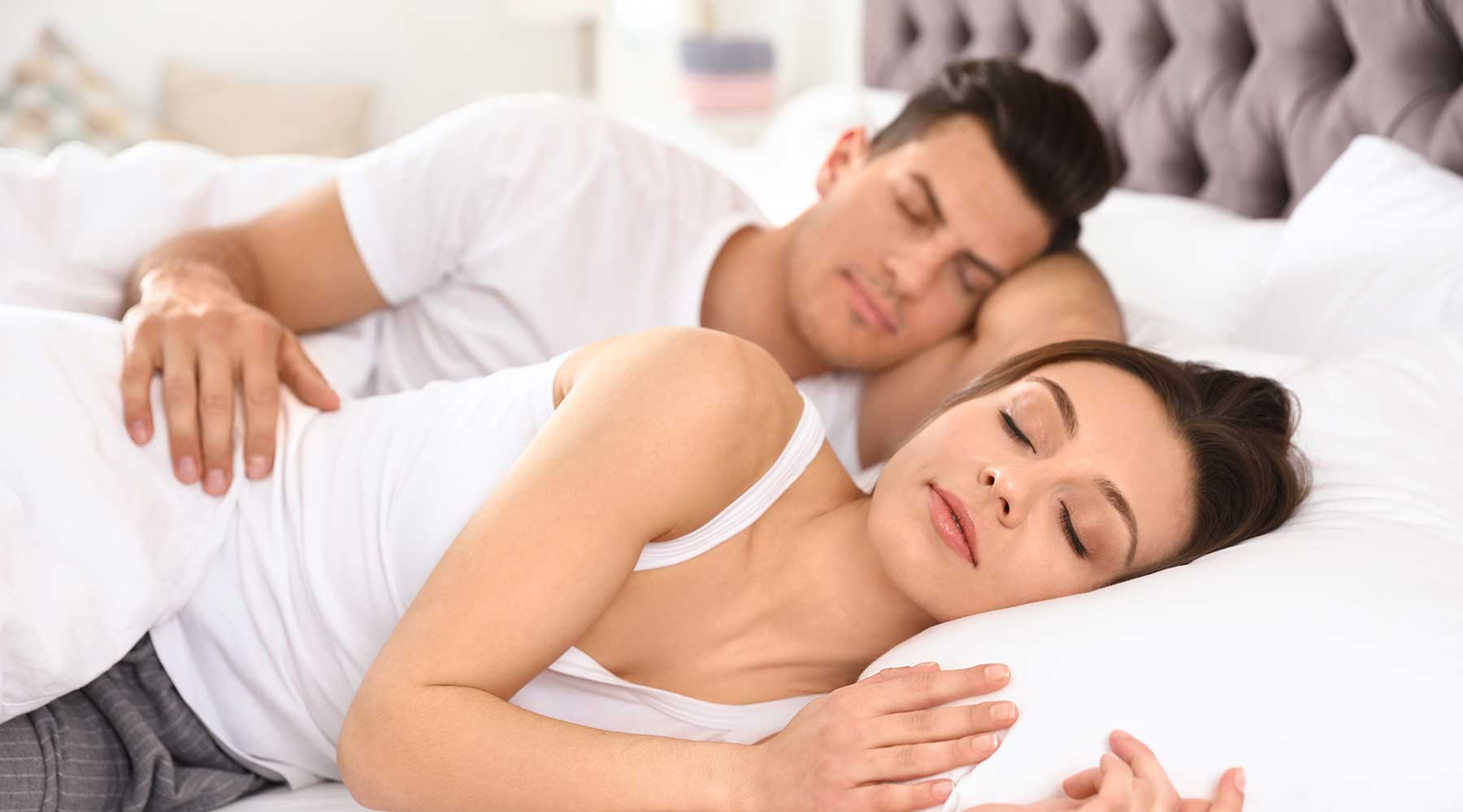 A man and woman sleeping in a bed