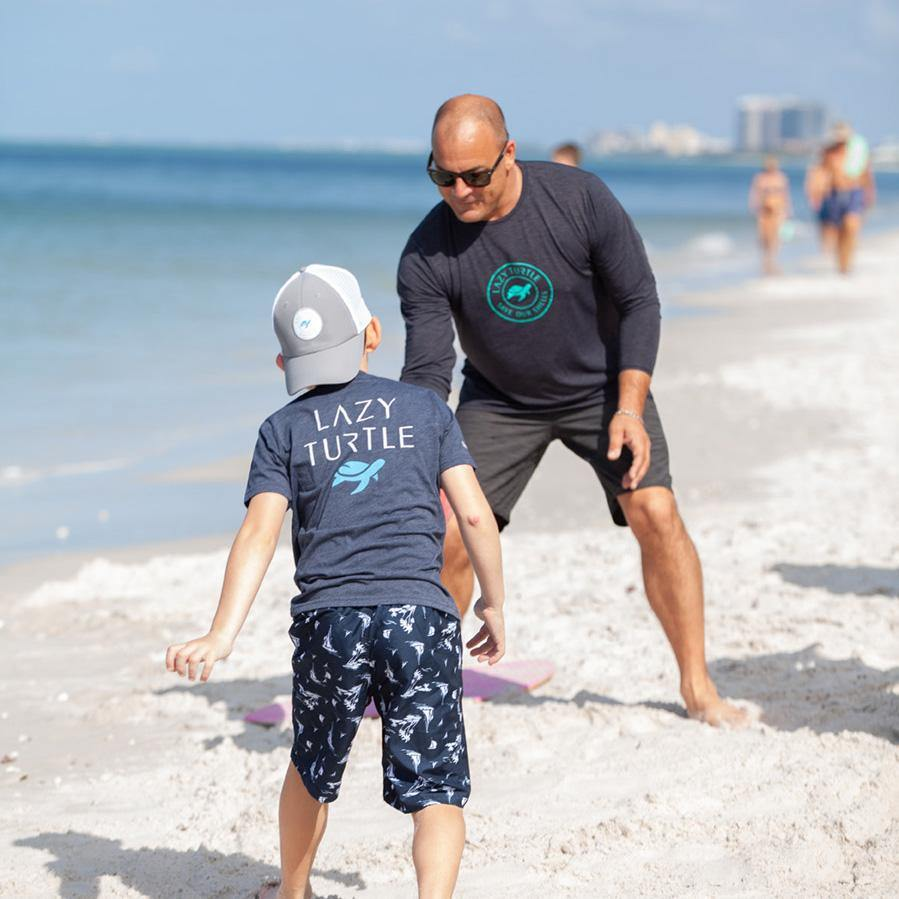Man wearing Coastal Sun Safe Long Sleeve playing on beach with kid