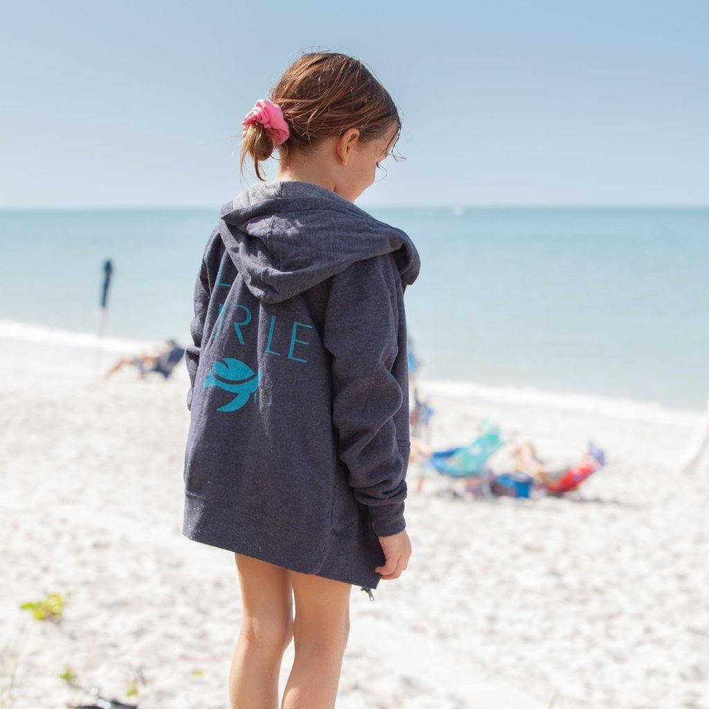 Side view of girl wearing AJ Hoodie on beach