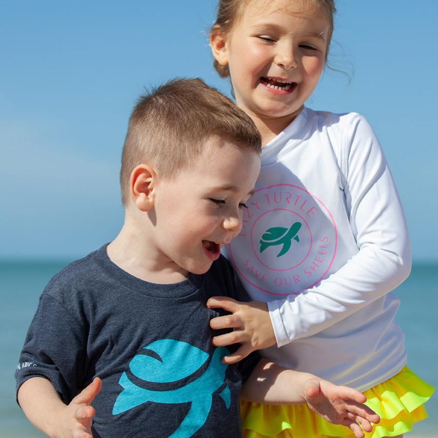 Boy wearing Lizzy Tee on beach with girl
