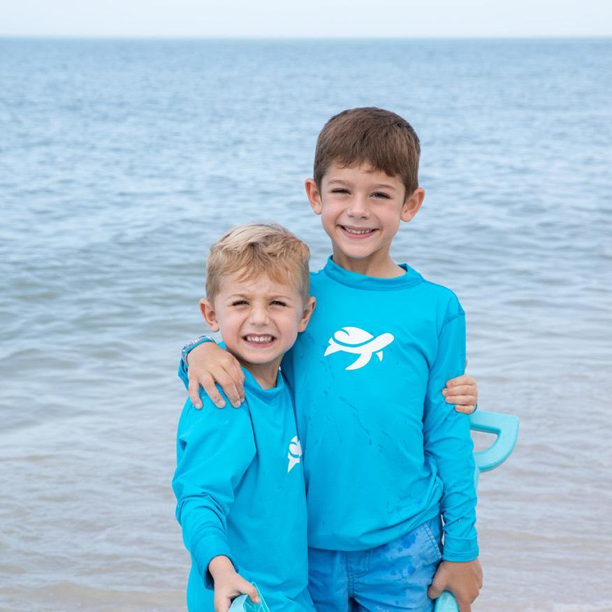 Two boys wearing Sand Castle Sun Safe Long Sleeve on beach