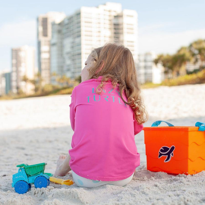 Back view of girl wearing Sand Castle Sun Safe Long Sleeve on beach