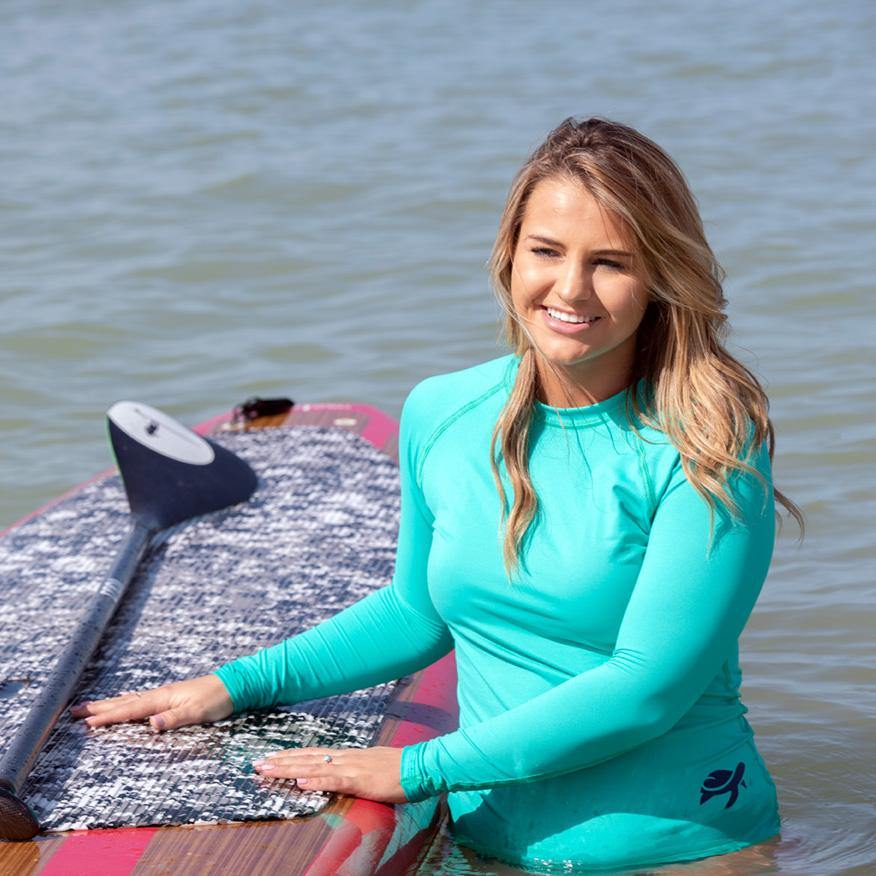 Woman wearing Wave Sun Safe Long Sleeve with paddle board.