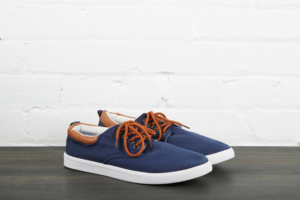Dark blue, low-top shoes with a white midsole, brown lace, black back tab, and white lining.