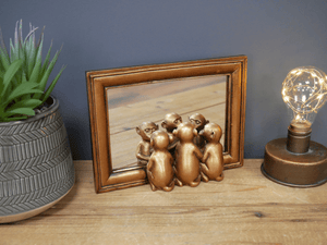 An adorable small free standing mirror with three sitting Monkeys looking at their reflections In a rectangle design mirror with a gold slightly distressed frame/GiftworksStores, Ennis&Galway