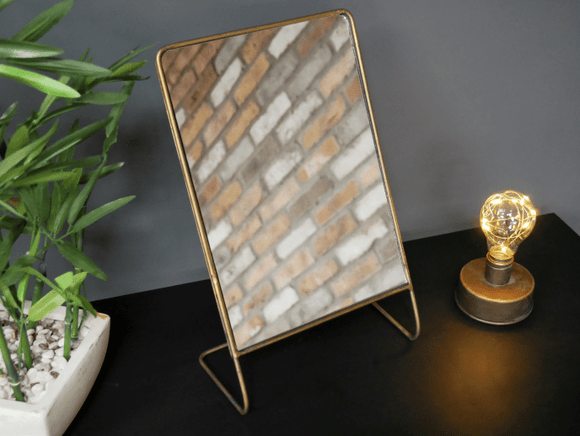 Free Standing Mirror, The mirror is a free-standing table mirror with a warm metallic copper finish. Standing on a simple wireframe/Giftworks, Ennis&Galway