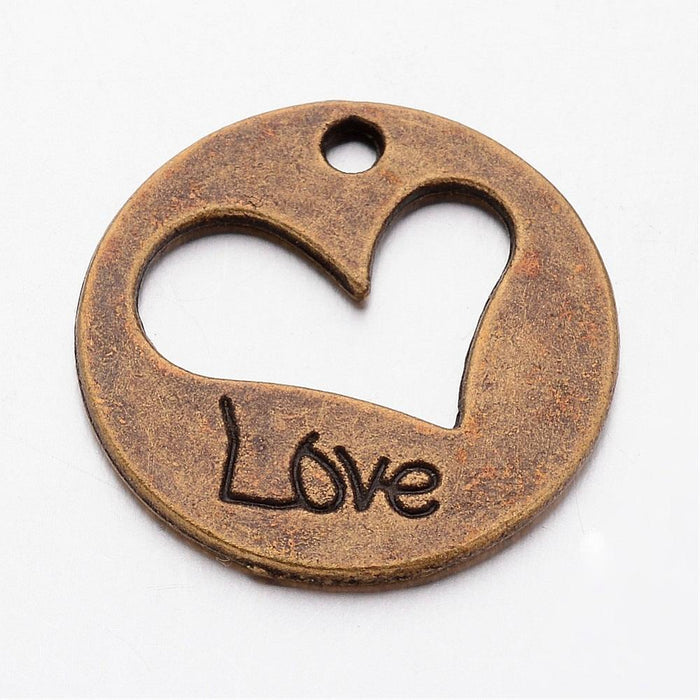 close up of a bronze jewelry charm that is heart shaped with love stamped