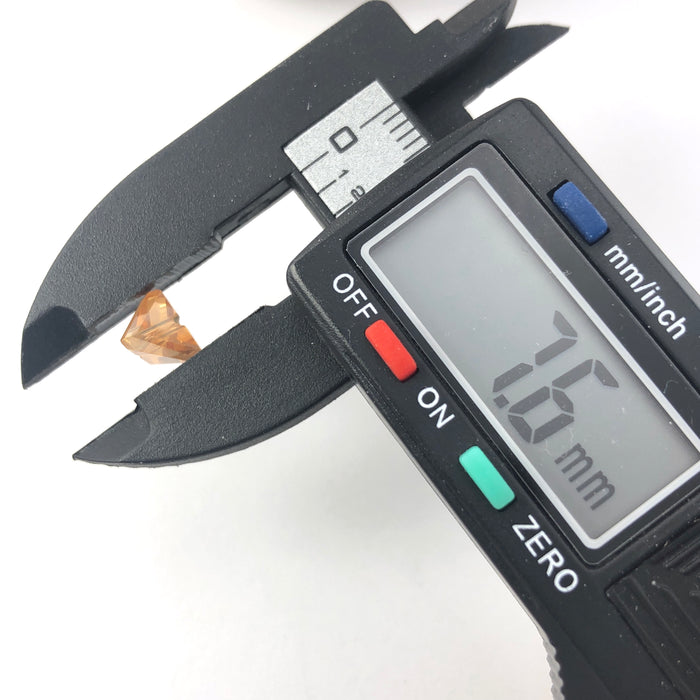 amber colour triangle shaped jewelry beads, on an electronic ruler that reads 7.6mm