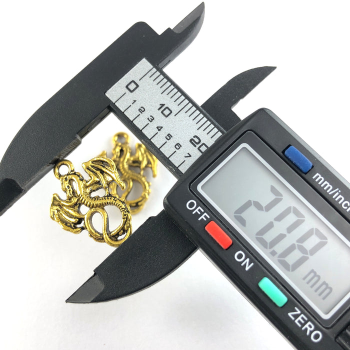Antique gold coloured jewerly pendant that looks like a dragon, on a digital ruler widthwise that reads 20.8mm