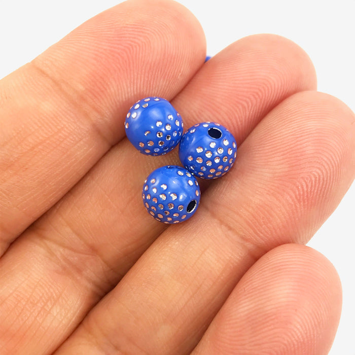 Royal blue round acrylic beads with silver sparkles on a hand