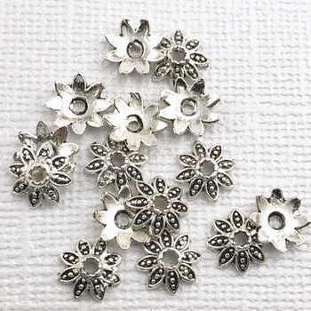 pile of flower shaped silver beads caps